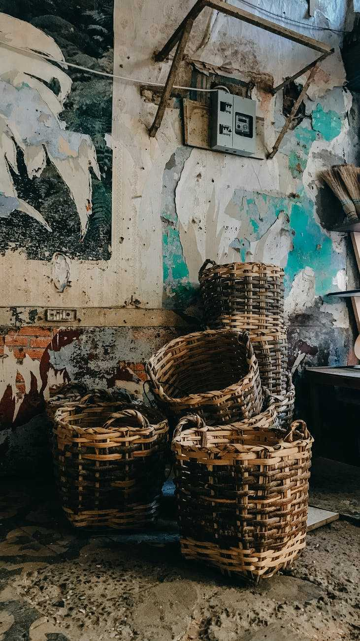 wicker baskets against rough wall with painting