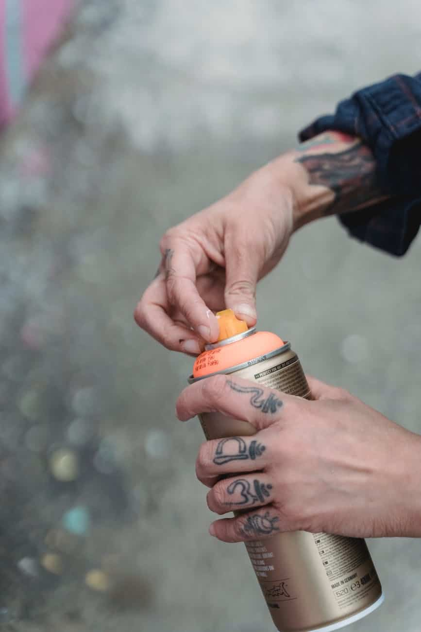 close up shot of a person holding a spray paint